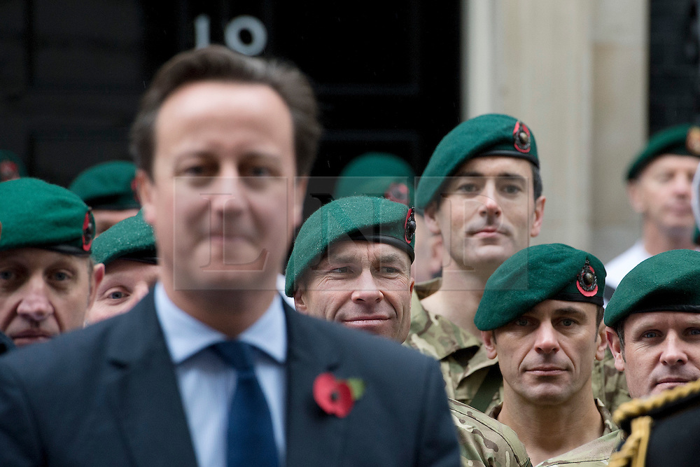 © London News Pictures. 10/11/2012. London, UK. British Prime Minister David Cameron posing with Royal Marines from Commando 999 (Royal Marines who serve with the UK emergency services)  outside number 10 Downing Street before the Marines take part in a speed march around London in record time to raise funds for wounded service personnel. The charity event takes place on Remembrance weekend.  Photo credit: Ben Cawthra/LNP