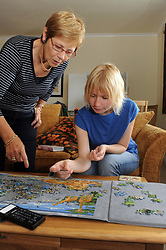 Young woman with learning disabilities doing jigsaw with her support worker; Skipton; Yorkshire