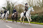 Horses and their riders take part in the traditional Chiddingfold, Leconfield and Cowdray Boxing Day Hunt as it leaves on the main road from the kennels at Petworth House in Petworth Park, West Sussex, UK on December 26, 2018