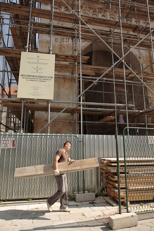 Workman carrying a plank for building the scaffold over the cathedral narthex, during restoration of the 13th century Radovan sculptures there.  It was disappointing not to see them!
