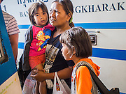 04 JANUARY 2015 - BANGKOK, THAILAND:  A family waits to board a bus at the Mo Chit Bus Station. Mo Chit, also called the Northern Bus Station, is the largest bus station in Thailand. Buses from Mo Chit go to most places in Thailand, including the Isan region, the northern cities of Chiang Mai and Chiang Rai, and the Burmese border. Millions of Thais hit the road Sunday returning to Bangkok after the long weekend New Year holiday. Train stations and trains were packed and the state owned bus company scheduled thousands of extra buses to handle the demand.   PHOTO BY JACK KURTZ