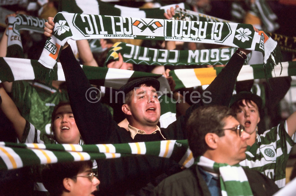 Celtic fans at the Parkhead ground, Glasgow wave their flags and sing their teams' songs. Celtic have a strong following of mostly Irish Catholics and are bitter rivals to the city's other team, Glasgow Rangers.