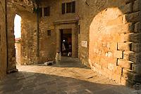 Sun glows an arch onto the wall near piazzetta di San Francesco in Montepulciano, Italy.