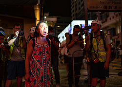 Hong Kong, China. 13th October 2019. Woman suspected of being pro-Beijing is assaulted by pro-democracy protestors in Mongkok district in Kowloon on Sunday evening. This incident was one of several throughout Hong Kong on Sunday which saw acts of vandalism carried out by a minority in the pro-democracy movement. Female protestor in police spotlight shouts abuse at police in Mongkok.Iain Masterton/Alamy Live News.