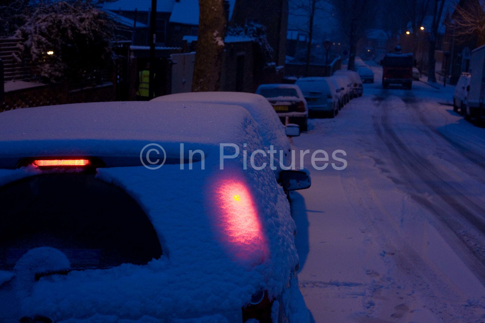 As blue dawn light becomes another wintry day in south London, the glow of a car's brake lights shines through a covering of fresh snow. The driver has only swept the vehicle's back window with a rear wiper but with her foot on the brake pedal, she is about to set off on a drive to work this morning on roads that have controversially, not been gritted or salted by council highway workers. The surface is therefore still snowy in this residential area of Herne Hill, SE24, London and is a treacherous surface on which to maintain wheel and tyre (tire) traction and many accidents will result, including the heavy lorry (truck) which is about to climb this hill and which will soon prevent him from going much further.