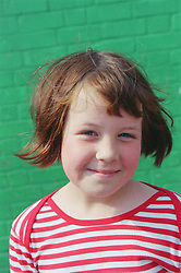 Portrait of young girl standing outside smiling,