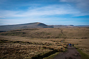 A group of adult and child ramblers walk along the dirt track towards the summit of Pen Y Fan Mountain in Brecon Beacons National Park, Wales, Powys, United Kingdom. Pen Y Fan is the highest point in the Brecon Beacons hill and mountain range in South Wales. The National Park was established in 1957 due to the spectacular landscape which is rich in natural beauty.