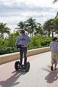 A young man riding a Segway space age transport machine along Miami Beach