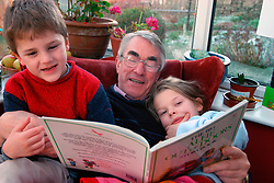 Grandfather reading Alfie book to his young grandchildren; UK