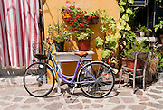 """Woman's bicycle, potted plants, chair. Burano, known for knitted lacework, fishing, and colorfully painted houses, is a small archipelago of four islands linked by bridges in the Venetian Lagoon, northern Italy, Europe. Burano's traditional house colors are strictly regulated by government. The Romans may have been first to settle Burano. Romantic Venice (Venezia), """"City of Canals,"""" stretches across 117 small islands in the marshy Venetian Lagoon along the Adriatic Sea in northeast Italy, between the mouths of the Po (south) and Piave (north) Rivers. Venice and the Venetian Lagoon are honored on UNESCO's World Heritage List."""