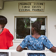 INDIVIDUAL(S) PHOTOGRAPHED: N/A. LOCATION: St. Damien Hospital, Nos Petits Frères et Sœurs, Tabarre 41 Commune, Haïti. CAPTION: Patients at St. Damien Hospital wait in line at the pharmacy window for their medication.