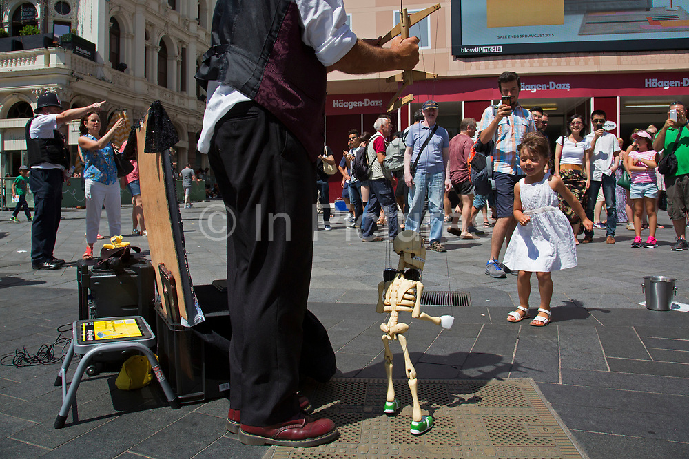 Summertime in London, England, UK. Street entertainer performs his incredible dancing and singing puppet show to an entralled crowd of onlookers in Leicester Square, one of London's busiest tourism hot spots. His skeleton man puppet dances away whilst singing to old time music. Gathered children engage with the skeletal figure as if he were real.