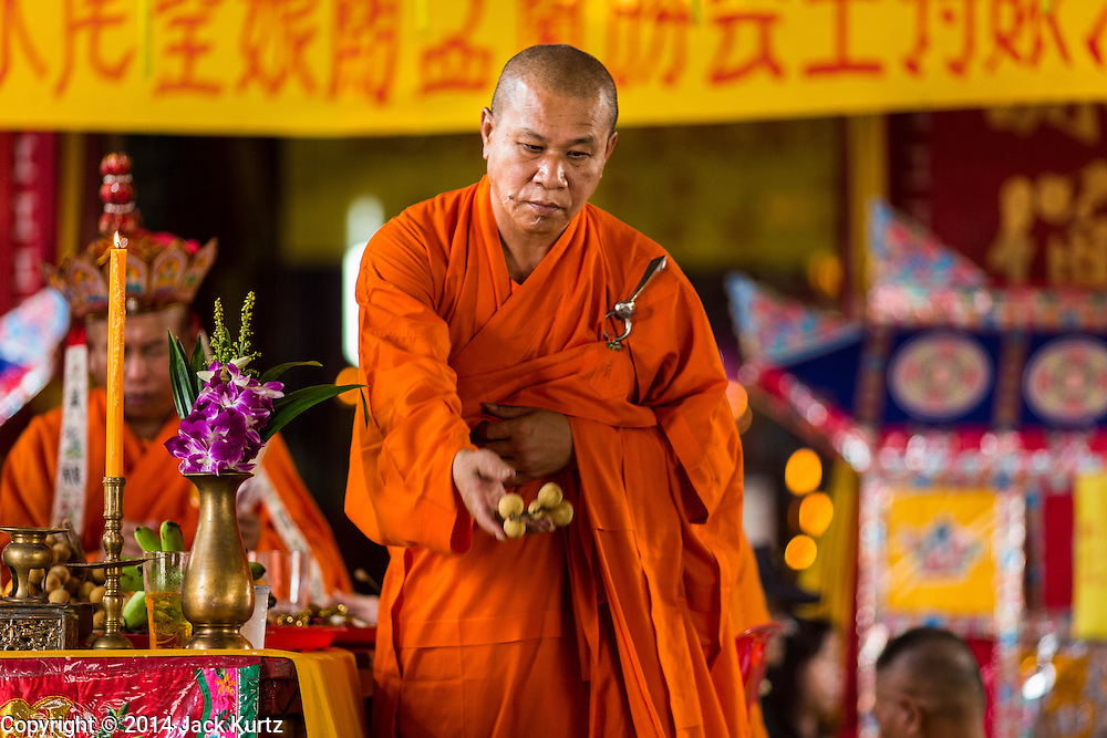 """09 AUGUST 2014 - BANGKOK, THAILAND:  A Vietnamese Mahayana Buddhist monk throws fruit to the crowd during a Ghost Month service at the Ruby Goddess Shrine in the Dusit section of Bangkok. The seventh month of the Chinese Lunar calendar is called """"Ghost Month"""" during which ghosts and spirits, including those of the deceased ancestors, come out from the lower realm. It is common for Chinese people to make merit during the month by burning """"hell money"""" and presenting food to the ghosts. At Chinese temples in Thailand, it is also customary to give food to the poorer people in the community.        PHOTO BY JACK KURTZ"""