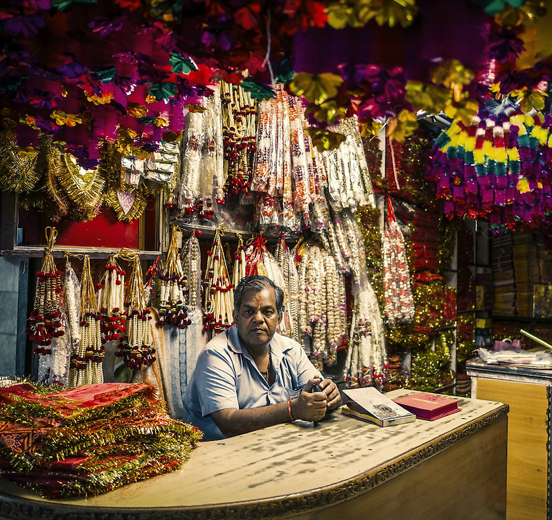 Street market vendors selling decorative items many used in Diwali or to decorate temples and god figures. This shop is in located in one of the bazaars of the old city of Jaipur.