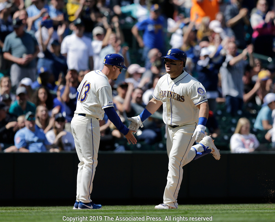 Seattle Mariners' Daniel Vogelbach is congratulated by third base coach Chris Prieto after hitting a home run against the  Minnesota Twins during a baseball game, Sunday, May 19, 2019, in Seattle. (AP Photo/John Froschauer)