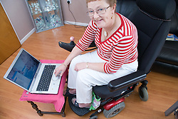 Older woman wheelchair user working on a lap top computer,