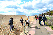 People enjoy the Sunny weekend as they walk along the Brighton Beach on Sunday, April 11, 2021. <br /> On Monday, April 12, England enters the next stage of government's roadmap out of lockdown, when the non-essential shops, outdoor hospitality, and personal services including hairdressing can open again. (Photo/ Vudi Xhymshiti)