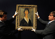 © Licensed to London News Pictures. 02/02/2012, London, UK. Two gallery assistants hang 'Jeune file aux cheveux noirs' by the italian artist Amedeo Modigliani. The painting is expected to fetch 700,000-1,000,000GBP. Photo call at Bonhams, London for Impressionist and Modern Art Auction preview. Photo credit : Stephen Simpson/LNP