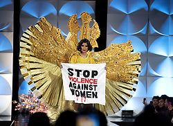 """December 6, 2019, Atlanta, GA: JÅ""""lia Horta, 25, representing Brazil in Miss Universe pageant,  reveals a ÔStop violence against womenÃ• banner during the pageantÃ•s national costume segment Friday night Dec. 6, in Atlanta. The pageant features contestants from 90 countries, with 20 finalists to be announced Sunday Dec. 8 in the televised final competition. (Credit Image: © Robin Rayne/ZUMA Wire)"""