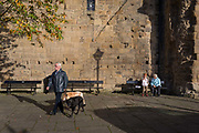 Locals sit in afternoon sunshine beneath the tall outer wall of Hexhams Moot Hall, on 29th September 2017, in Hexham, Northumberland, England. Originally, this gatehouse guarded the hall of the archbishops of York who were the Lords of the manor of Hexham for nearly 500 years until 1545. In later centuries the gatehouse became the setting for the Quarter Sessions of county magistrates and for the meetings of the towns Borough Courts, Since then it has been called the Moot Hall.