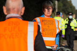 Insulate Britain climate activists wait under arrest by Surrey Police on the hard shoulder of the M25 after blocking the clockwise carriageway between Junctions 9 and 10 on 21st September 2021 in Ockham, United Kingdom. Activists briefly halted traffic on both carriageways of the motorway as part of a campaign intended to push the UK government to make significant legislative change to start lowering emissions.