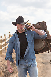 Rugged cowboy with a saddle over his shoulder walking on a dirt road on a ranch