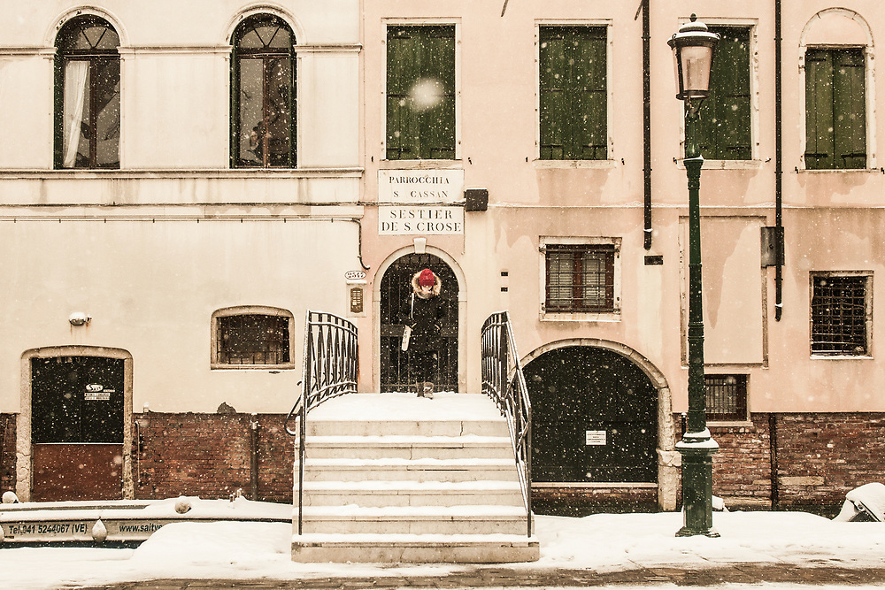 """VENICE, ITALY - 28th FEBRUARY/01st MARCH 2018<br /> A girl exits from her house during a snowfall in Venice, Italy. A blast of freezing weather called the """"Beast from the East"""" has gripped most of Europe in the middle of winter of 2018, and in Venice A snowfall has covered the city with white, making it fascinating and poetic for citizen and tourists.   © Simone Padovani / Awakening"""
