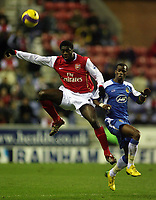Photo: Paul Thomas.<br /> Wigan Athletic v Arsenal. The Barclays Premiership. 13/12/2006.<br /> <br /> Kolo Toure (L) of Arsenal tries to get away from Henri Camara.