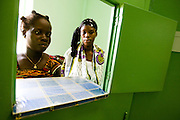 Brou Adjua Thérèse (left) and Konaté Fatouma wait to purchase drugs at the pharmacy of the NDA health center in Dimbokro, Cote d'Ivoire on Friday June 19, 2009..