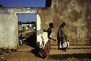 "A mother carries her child past Shalom House, an orphanage for war orphans.<br /> They now live at the orphanage and home called Shalom House founded by Marguerite Barankitse (known as the 'Angel of Burundi') in 1994. During the genocide, Barankitse, at great personal risk, managed to save 25 orphans, Hutu, Tutsi and Twa and built a home for them. Currently, she has helped more than 10,000 orphans and separated children who can grow up in an ""extended adopted family"" in security, education and love."