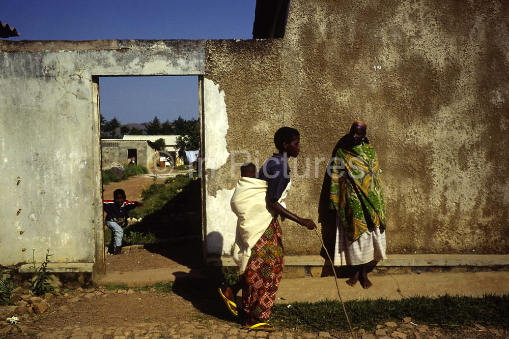 """A mother carries her child past Shalom House, an orphanage for war orphans.<br /> They now live at the orphanage and home called Shalom House founded by Marguerite Barankitse (known as the 'Angel of Burundi') in 1994. During the genocide, Barankitse, at great personal risk, managed to save 25 orphans, Hutu, Tutsi and Twa and built a home for them. Currently, she has helped more than 10,000 orphans and separated children who can grow up in an """"extended adopted family"""" in security, education and love."""