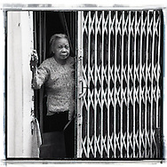 An old vietnamese woman stands in her house, just behind a gate. She smiles and looks happy