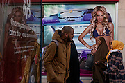 A man walks two Muslim women and an image of a girl wearing a bikini in a high-street advert for sunbeds, on 26th December 2016, in Bristols Broadmead, England UK.