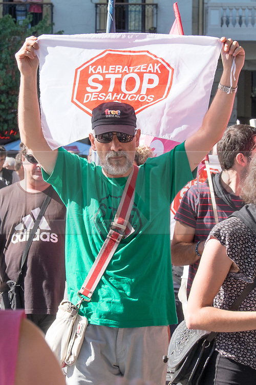 """@Licensed to London News Pictures 17/08/17. San Sebastian, Basque Country, Spain. Protestors leading an anti-tourism march today through the crowded streets of the Basque town of San Sebastian in Spain. The banner translation from Basque is """" Stop the evictions"""". Following on from similar demonstrations in Barcelona protestors in San Sebastian are protesting against the  over-tourism of their country.  Photo credit: Manu Palomeque/LNP"""