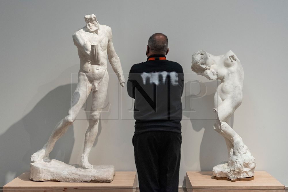 """© Licensed to London News Pictures. 11/05/2021. LONDON, UK. A staff member poses with (L) """"Pierre de Wissant Nude, without Head or Hands, Large Model"""", 1886, and """"The Inner Voice"""", 1896, both by Auguste Rodin. Preview at Tate Modern of """"The Making of Rodin"""", a major new exhibition of over 200 sculpture works by Auguste Rodin, many of which have never been shown outside France. The exhibition marks the reopening of the museum as the UK government eases certain coronavirus lockdown restrictions and is open 18 May to 21 November.  Photo credit: Stephen Chung/LNP"""