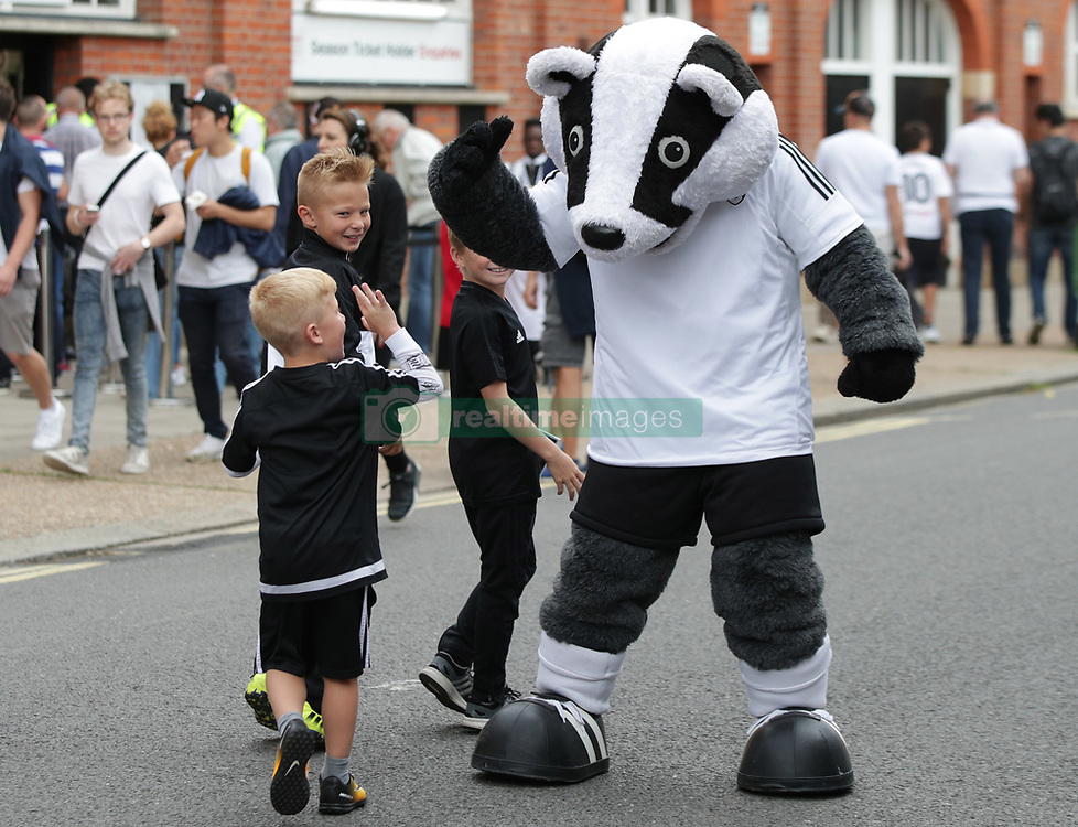 Fulham fans greet the club mascot Billy the badger