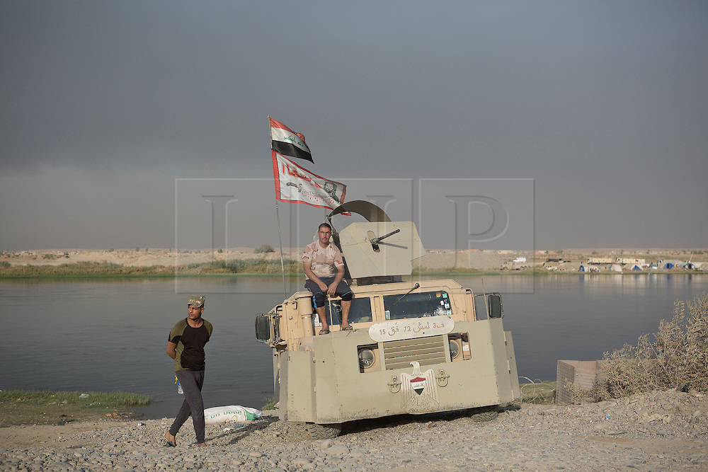 Licensed to London News Pictures. 20/10/2016. Iraqi Shia militia are seen with their armoured Humvee at a checkpoint on the Tigris River near the town of Qayyarah.<br /> <br /> Since being retaken from the Islamic State the town of Qayyarah has become an important staging post for the Iraqi Army, and some US support elements, in the buildup to the Mosul offensive.<br /> <br /> <br /> Photo credit: Matt Cetti-Roberts/LNP