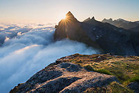Summer fog hides the sea while the midnight sun shines overhead from the summit of Helvetestind, Moskenesøy, Lofoten Islands, Norway