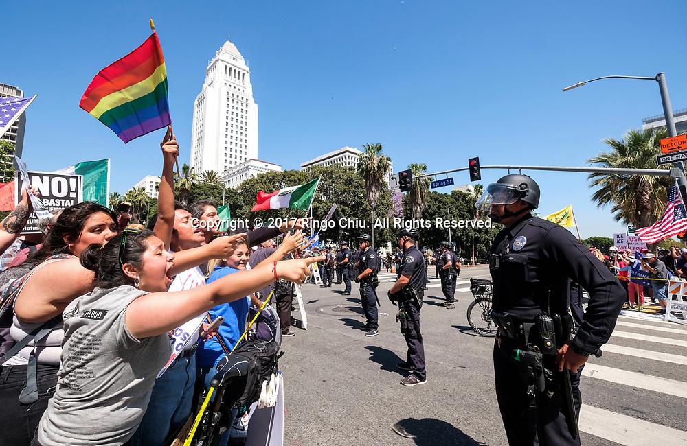 """5月1日,在美国洛杉矶,警察把参加""""五一""""国际劳动节游行的示威群众与特朗普总统的支持者分开。 当日,全美各城市的数以万计移民及其支持者集会抗议特朗普总统的移民政策,为工人权益发声。新华社发(赵汉荣摄)<br /> Police officers confront demonstrators at the end of May Day march in Los Angeles, the United States, May 1, 2017. Thousands of people took to the streets across the nation Monday to march in May Day rallies, calling for immigration reform, workers' rights and police accountability. (Xinhua/Zhao Hanrong)(Photo by Ringo Chiu/PHOTOFORMULA.com)<br /> <br /> Usage Notes: This content is intended for editorial use only. For other uses, additional clearances may be required."""