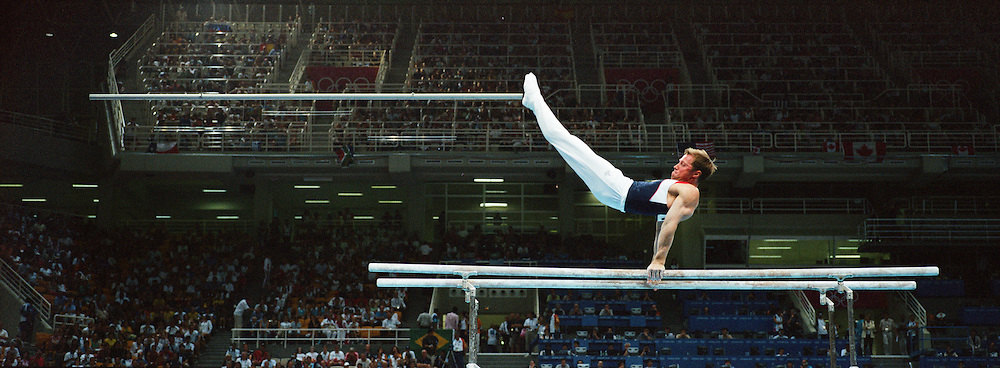 A  panoramic image of a male gymnast in action on the parallel bars during the Olympic Games, Athens, Greece. 28th August 2004. Photo Tim Clayton