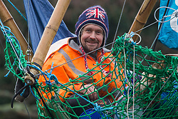 Denham, UK. 8th December, 2020. Dan Hooper, widely known as Swampy during the 1990s, smiles from a basket suspended from a bamboo tripod positioned in the river Colne. The climate and roads activist had occupied the tripod the previous day in order to delay the building of a bridge as part of works for the controversial HS2 high-speed rail link and a large security operation involving officers from at least three police forces, National Eviction Team enforcement agents and HS2 security guards was put in place to facilitate his removal.