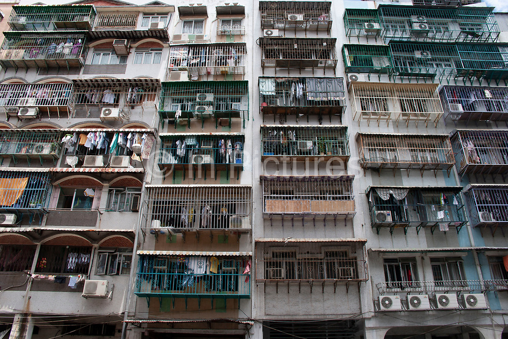 Busy apartment building in Macao, China. People live stacked on top of each other in small rooms within these blocks, with the exteriors covered in air conditioning units. Dripping their condensed water onto people passing below. Macau is an autonomous region on the south coast of China, across from Hong Kong. A Portuguese territory until 1999, it reflects a mix of cultural influences.