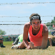 Colleen Ruddy in action at the barbed wire crawl obstacle during the Reebok Spartan Race. Mohegan Sun, Uncasville, Connecticut, USA. 28th June 2014. Photo Tim Clayton