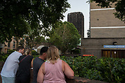 People gather opposite the burnt shell of Grenfell Tower on 16th June 2017 in West London, United Kingdom. The Grenfell Tower fire occurred on 14th June 2017 at the 24-storey block of public housing flats in North Kensington, West London. It caused at least 80 deaths and over 70 injuries, yet the actual numbers have yet to be confirmed