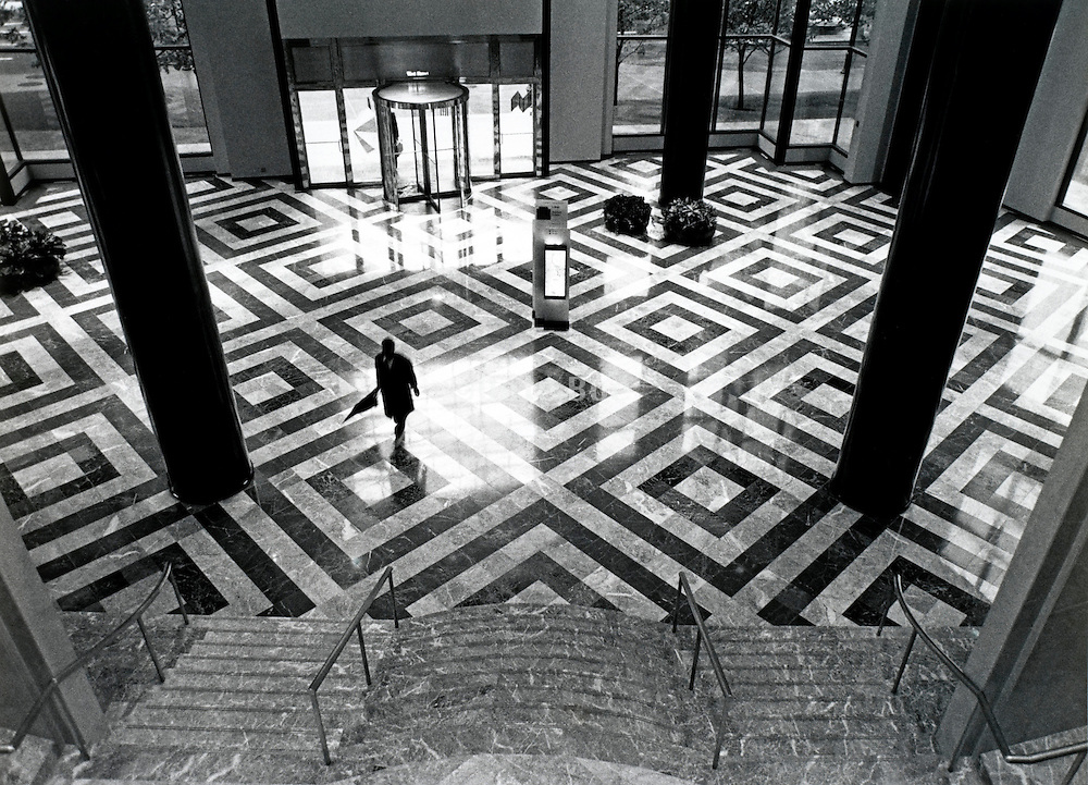 Interior of office building with silhouette of a man walking across the lobby holding a closed umbrella