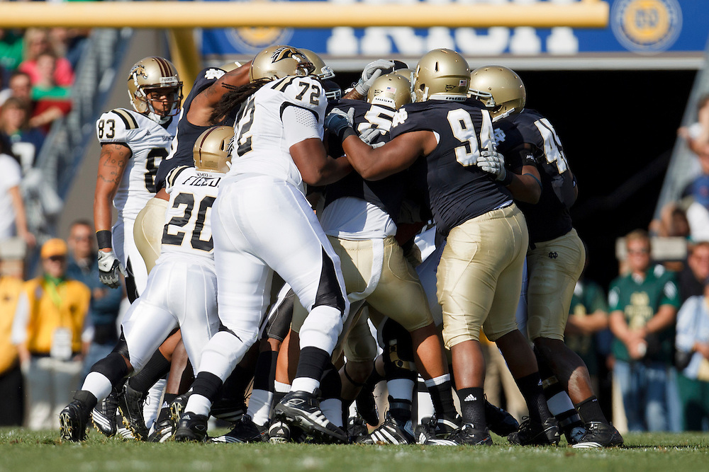 Players battle for yardage before the whistle during NCAA football game between Western Michigan and Notre Dame.  The Notre Dame Fighting Irish defeated the Western Michigan Broncos 44-20 in game at Notre Dame Stadium in South Bend, Indiana.
