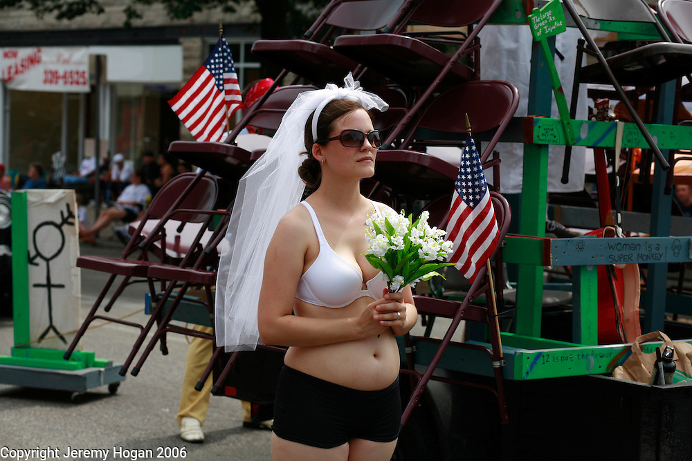 A woman walks wearing her bra and a wedding veil during the annual 4th of July parade in Bloomington, Indiana.