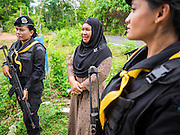 17 JUNE 2015 - RANGAE, NARATHIWAT, THAILAND:  Thai Army women Rangers talk to a Muslim woman during a mission to a Muslim village in Narathiwat province. There are 5 platoons of women Rangers serving in Thailand's restive Deep South. They generally perform security missions at large public events and do public outreach missions, like home wellness checks and delivering food and medicine into rural communities. The medics frequently work in civilian clothes because the Rangers found people are more relaxed around them when they're in civilian clothes. About 6,000 people have been killed in sectarian violence in Thailand's three southern provinces of Narathiwat, Pattani and Yala since a Muslim insurgency started in 2004. Attacks usually spike during religious holidays. Insurgents are fighting for more autonomy from the central government in Bangkok.    PHOTO BY JACK KURTZ