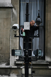 A man cleaning CCTV camera's in Central London, 2008. Photo By Andrew Parsons / i-Images