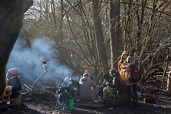 Harefield, UK. 19 January, 2020. Activists sit around a camp fire at the Colne Valley wildlife protection camp. Activists from Extinction Rebellion, Stop HS2 and Save the Colne Valley are attending a 'Stand for the Trees' event timed to coincide with tree felling work for HS2. 108 ancient woodlands are set to be destroyed by the high-speed rail link.